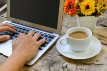 laptop with cup and flowers